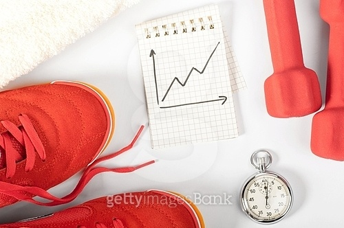 fitness progress. top view of notes, towel, red sneakers, barbells and stopwatch