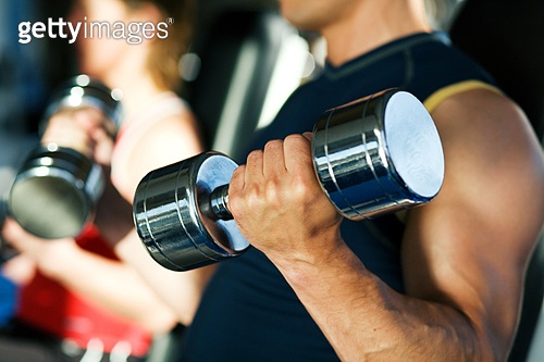 Strong man exercising with dumbbells in a gym, in the background a woman also lifting weights; focus on hand and dumbbell