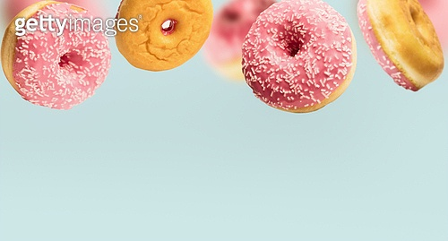 Falling or flying pink glazed doughnuts with sprinkles in motion at pastel blue background , border template