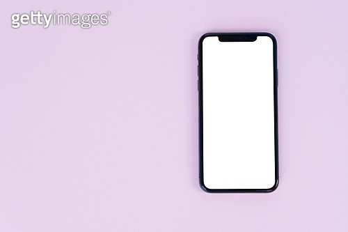 WARSAW, POLAND - DECEMBER 02, 2017: New Iphone X mobile phone on pink background with copy space. New Iphone X. New Iphone X