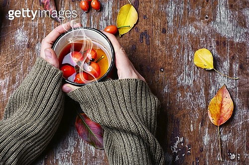 hot tea with berries rose hips. medicinal tea from the berries of the autumn rose in the hands