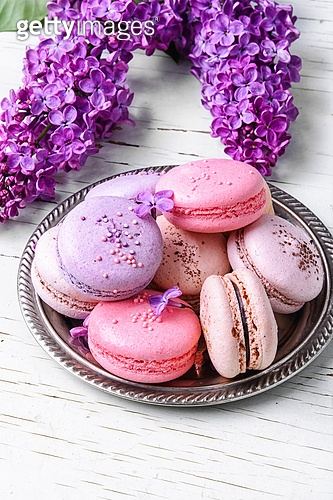 Sweet french macaroons. Colorful macarons cake and branch of lilac blossoms