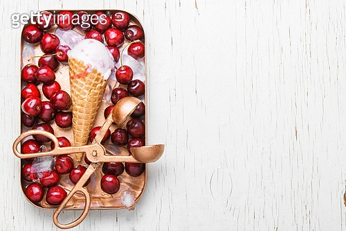 Ice-cream and sweet cherry. ice cream in waffle cones and cherry on white background