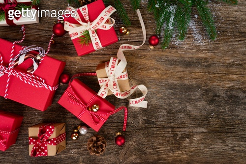 Christmas gift giving concept - christmas presents in red and white boxes on wooden table, flat lay scene. Christmas gift giving