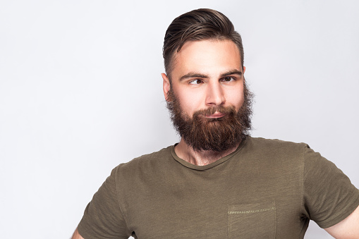 Portrait of crazy cross eyed bearded man with dark green t shirt against light gray background.