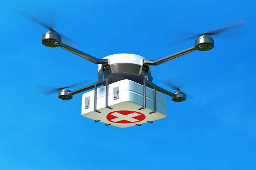 Drone with first aid kit on blue sky.