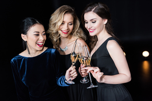 smiling women in stylish dresses clinking glasses with champagne