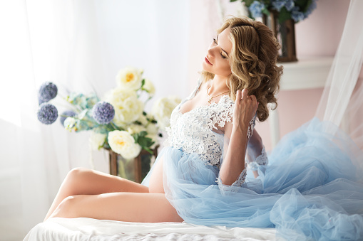 Pretty fashion pregnant girl is wearing blue boudoir dress sitting in bed