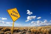 Open range road sign in mountain landscape, Colorado