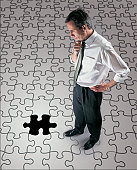 Mature Businessman Looking Down at an Incomplete Jigsaw Puzzle With His Hand on His Chin