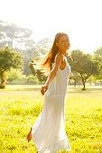 Carefree woman in sunlit field