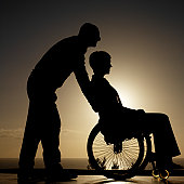 side view silhouette of a man pushing a woman sitting in a wheelchair