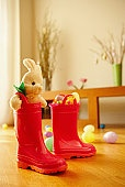Boots with rabbit and Easter eggs on floor