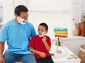 Father and son (4-7) with shaving cream on their faces, smiling
