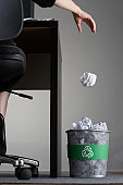 Person sitting at desk in office, throwing paper ball into trash can, low section