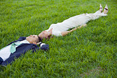 Businesspeople lying down in grass
