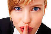 Close-up of a young woman with her finger on lips