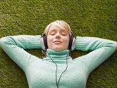 Woman wearing headphones, eyes closed, lying down