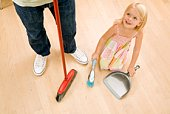 Girl sweeping floor with parent