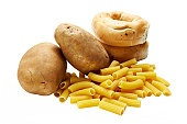 Potatoes, bagels, and uncooked macaroni on white background