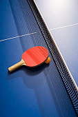 Table tennis paddle and ball on table