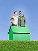 Couple standing near small model house