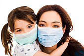 Daughter embracing mother as they both wear hospital masks