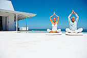 Couple practicing yoga beside the beach house
