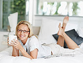 Happy mature lady lying on bed with coffee cup