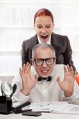 Angry boss harrasing her nerdy worker