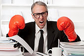 Stressed out businessman with boxing gloves