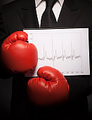 Tough businessman with red boxing gloves holding financial chart