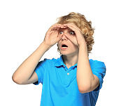 Teenage boy shielding eyes and looking
