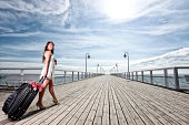 Beautiful woman girl sea mooring suitcase on a pier