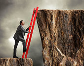 Businessman climbing ladder to get to higher level