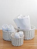 Clean towels in white wicker baskets