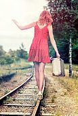 Woman walking on railroad tracks with suitcase