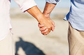 Close-Up Of Senior Couple Holding Hands On Beach