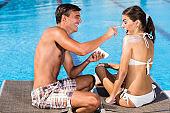 Man applying suntan lotion on woman's nose