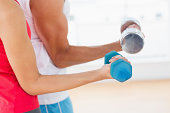 Mid section of a sporty young couple with dumbbells