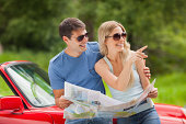 Cheerful young couple reading map