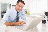 Smiling well dressed man using laptop in kitchen