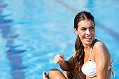 Woman with suntan lotion by the swimming pool