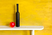 still-life with black bottle and apple
