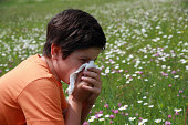 allergic boy to pollen and flowers with a handkerchief