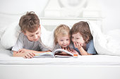 three boy read book indoors