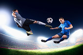 Two soccer players in mid-air kicking the ball