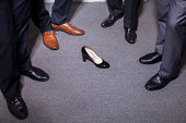 Businessmen standing around a woman's high heel