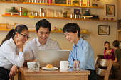 Three friends sitting in coffee shop, looking down at laptop