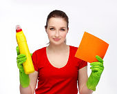 Woman with happy expression holding cleaning supplies